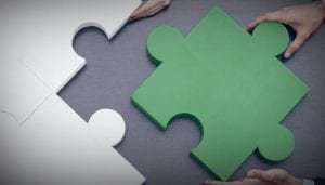 Large puzzle pieces in grey and green being moved into place by hands | About Midwest Medical Billing Services